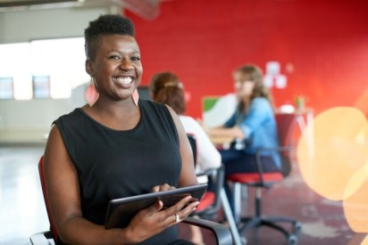 smiling professional woman holding a tablet