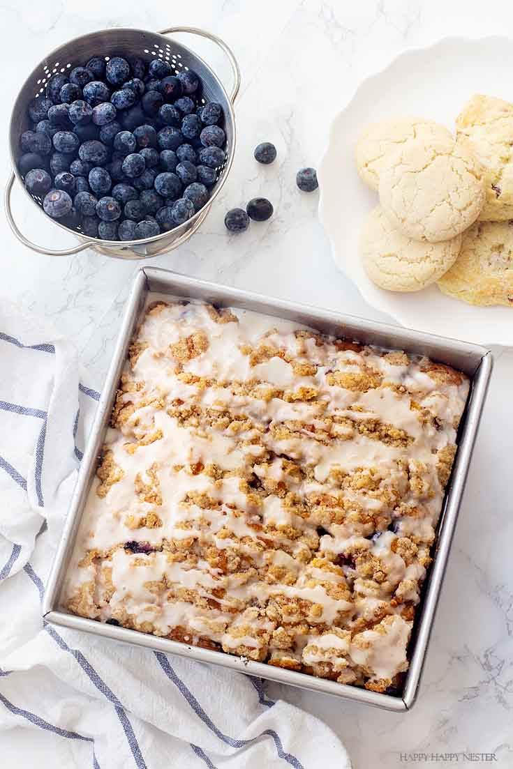 This dessert is The Best Blueberry Buckle Cake Recipe and is sure the perfect side to a cup of coffee or tea. Serve it as a dessert or as a morning blueberry coffee cake. This easy recipe makes an impressive cake with the crumble and delicious icing. #cake #coffeecake #blueberrydessserts #blueberries #desserts #pastry