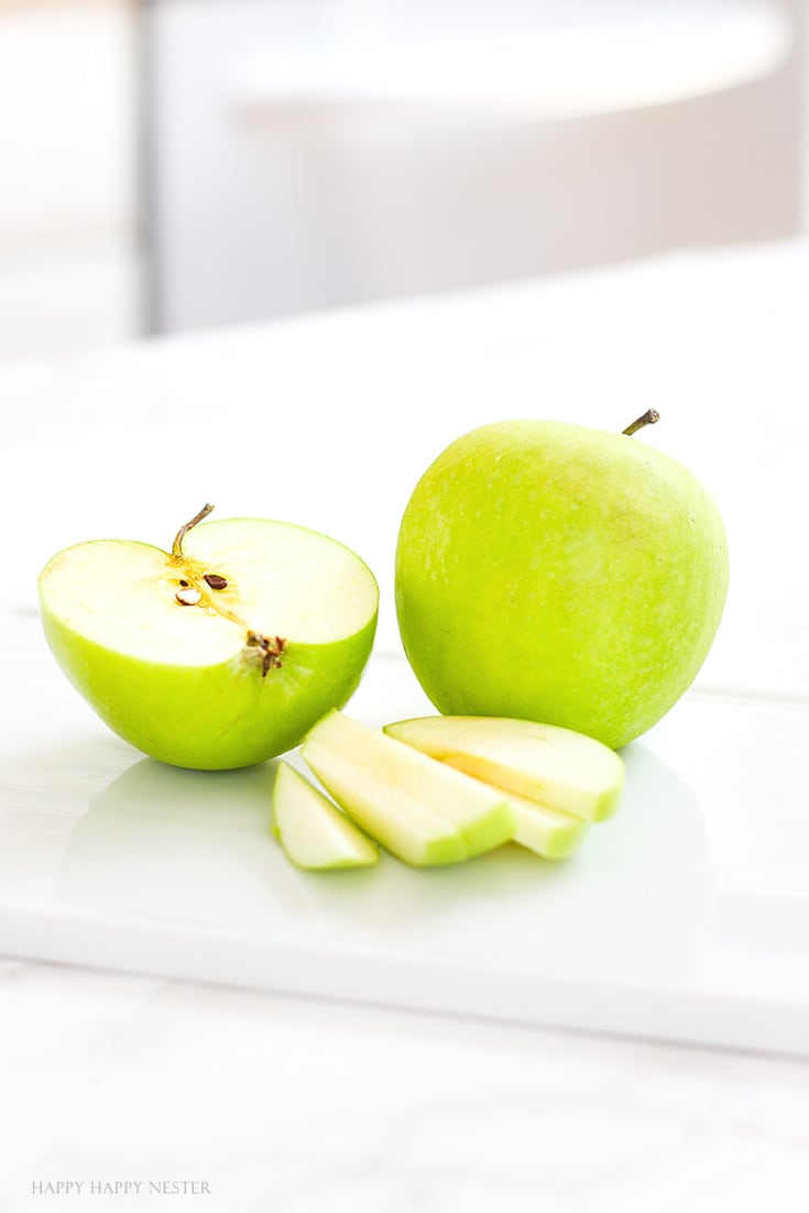 Green apples sliced and sitting on a white platter