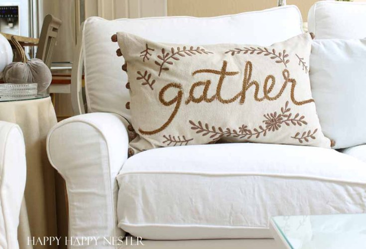 pillow with the words gather embroidered on it.