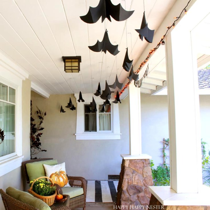 paper bats hanging from the white ceiling on a porch