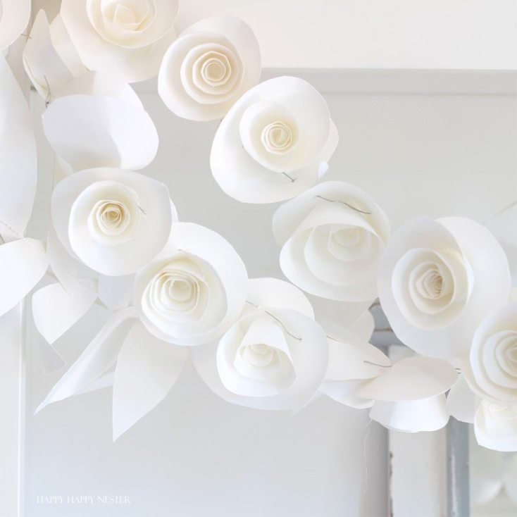 This fun paper garland DIY is not to be missed. You'll want to make both the leaf and rosettes garlands that you can hang anywhere in your home. Instant beauty wherever you place them. #craft #papercraft #paperflowers #garland #papergarland #weddingdecor #wedding