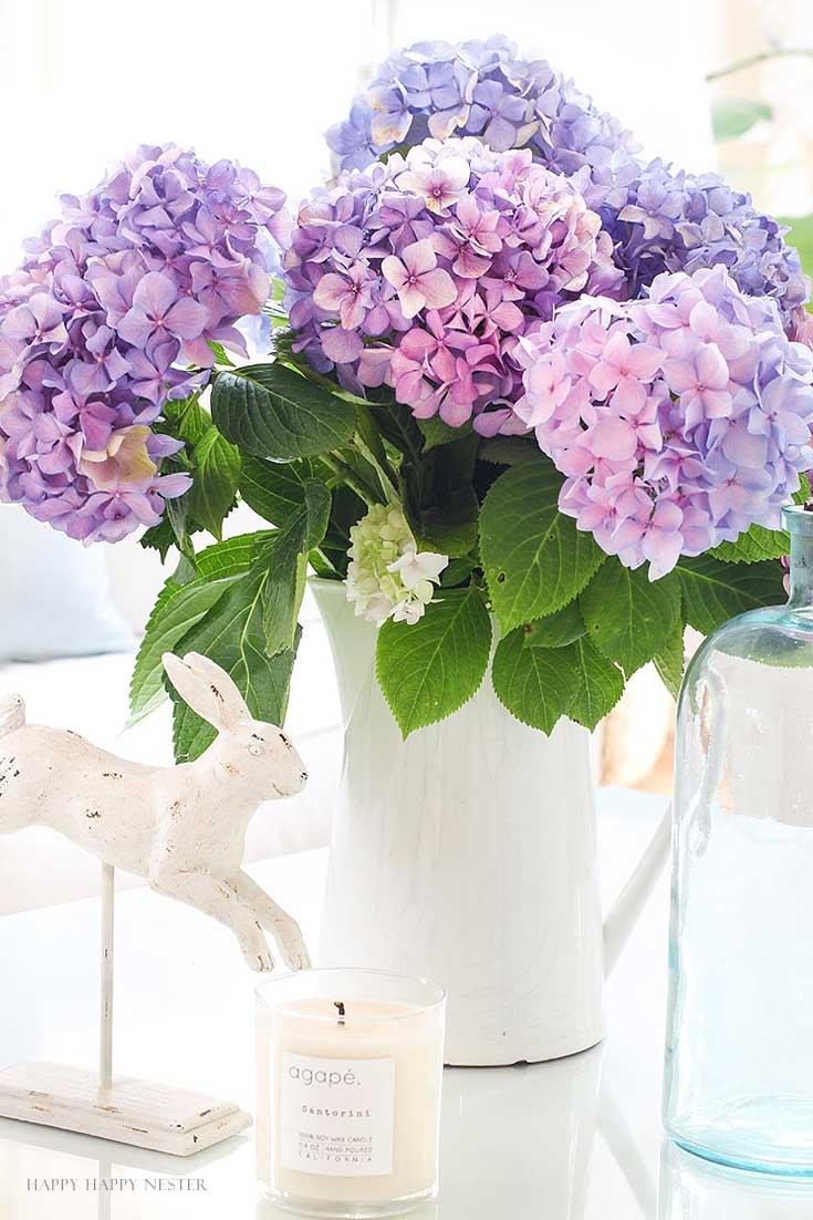 white pitcher with purple hydrangeas