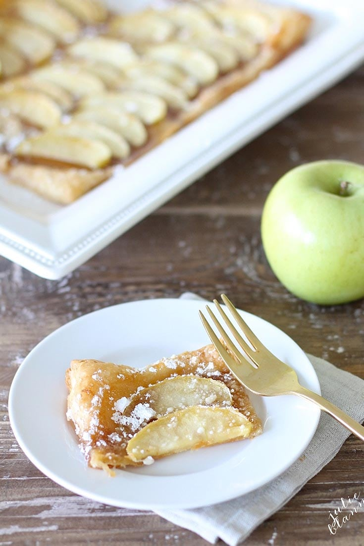 a slice of apple tart on a plate with a gold fork