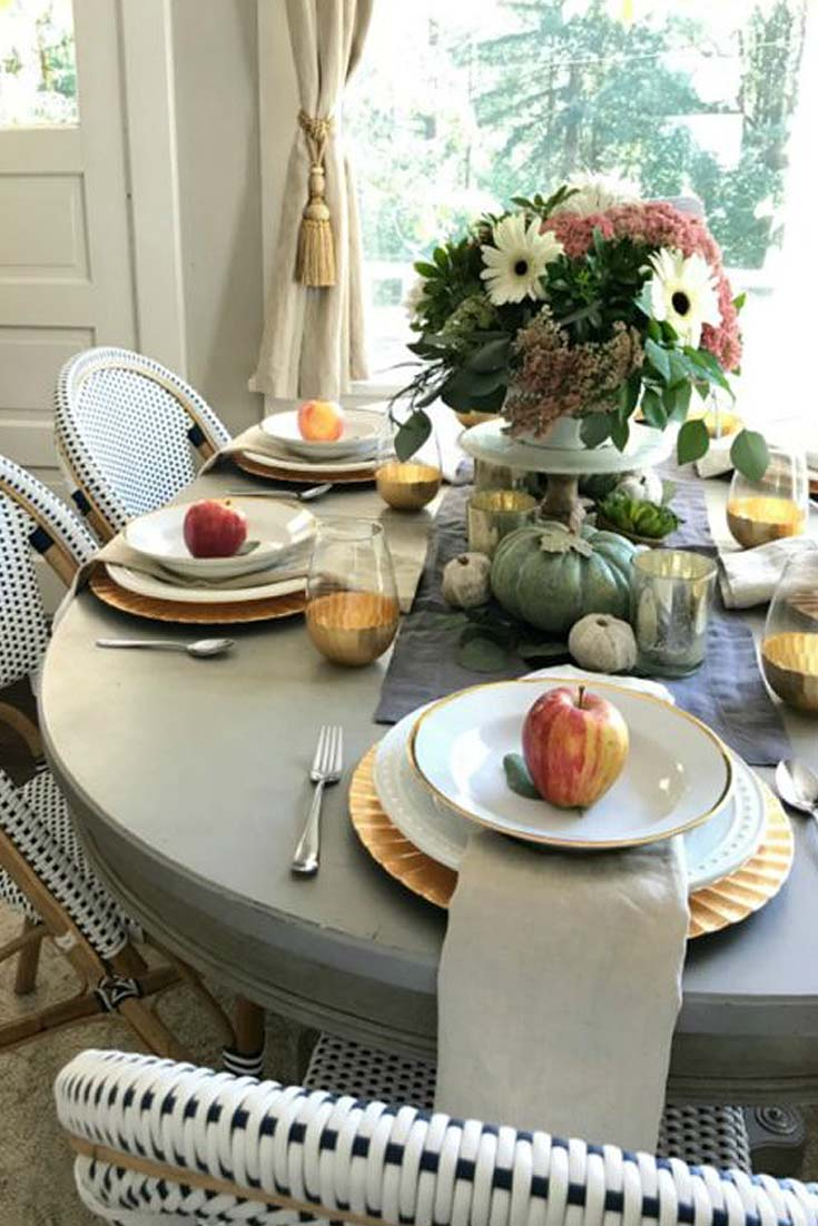 fall flowers in a vase on a table with apples on each place setting