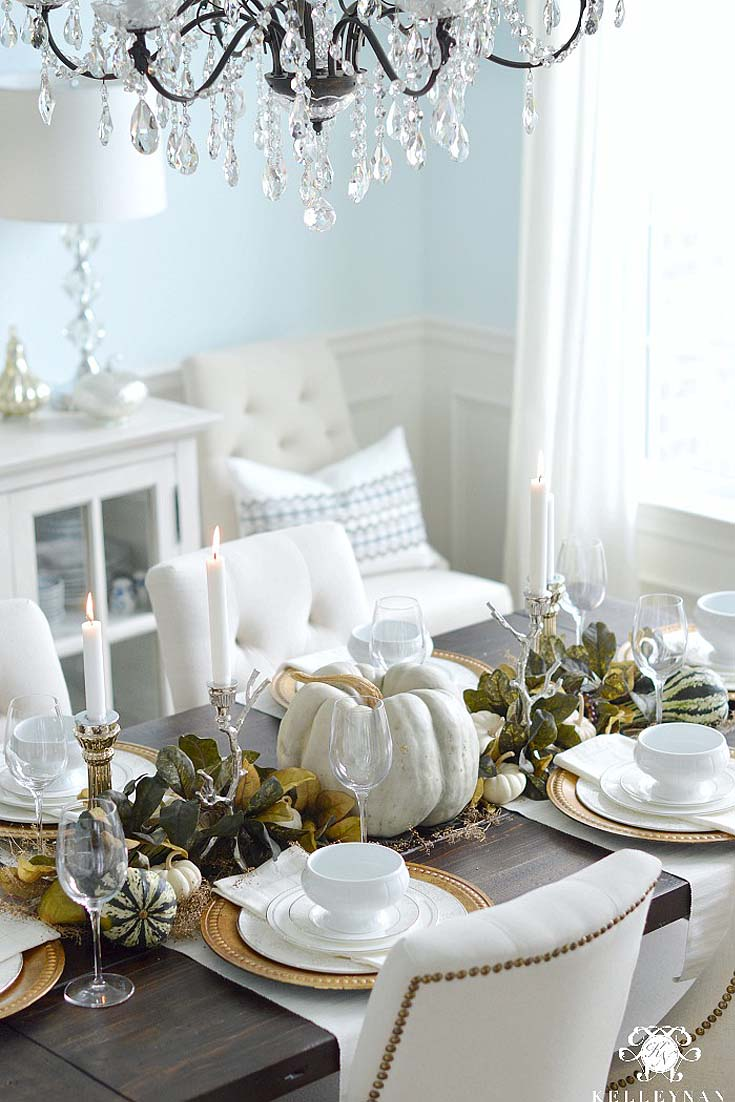 fall table with green leaves and white pumpkins