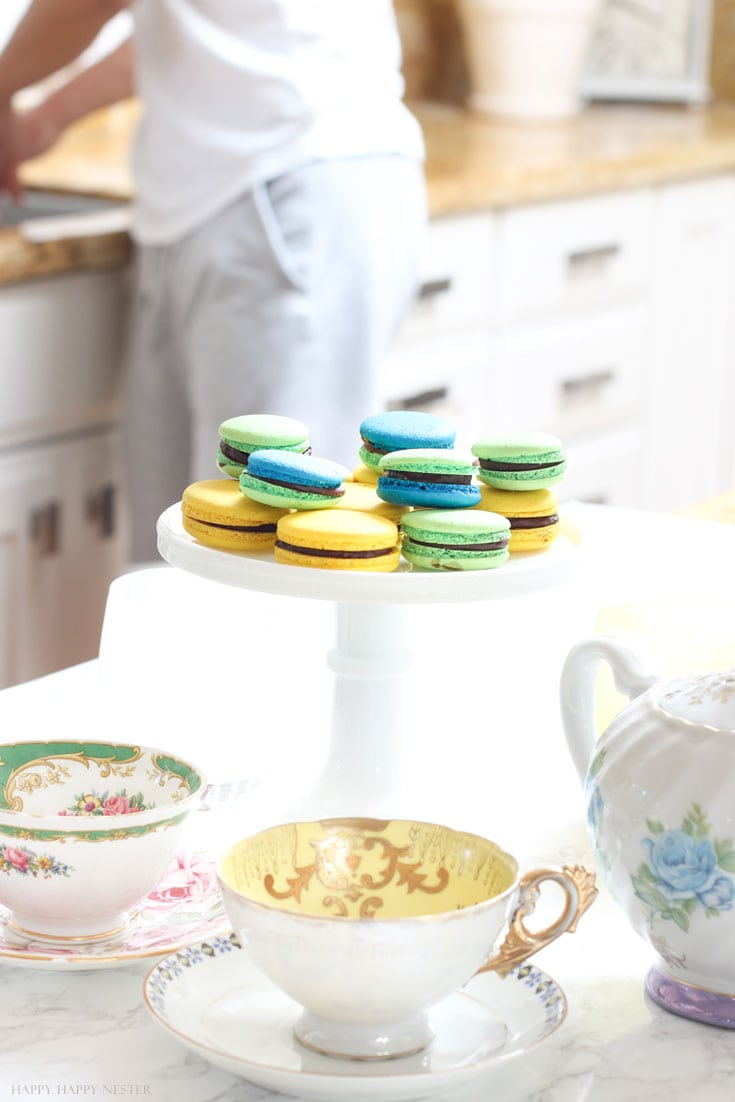macaron cookies on a white cake stand in a white kitchen
