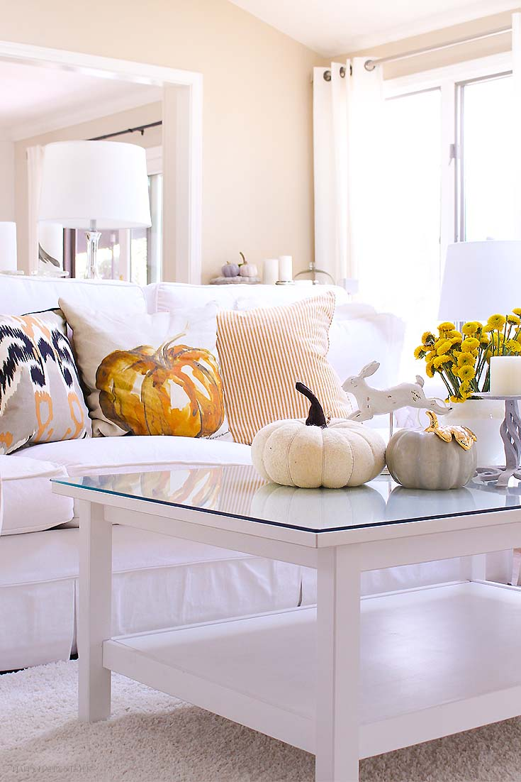 white living room with pumpkin on the coffee table