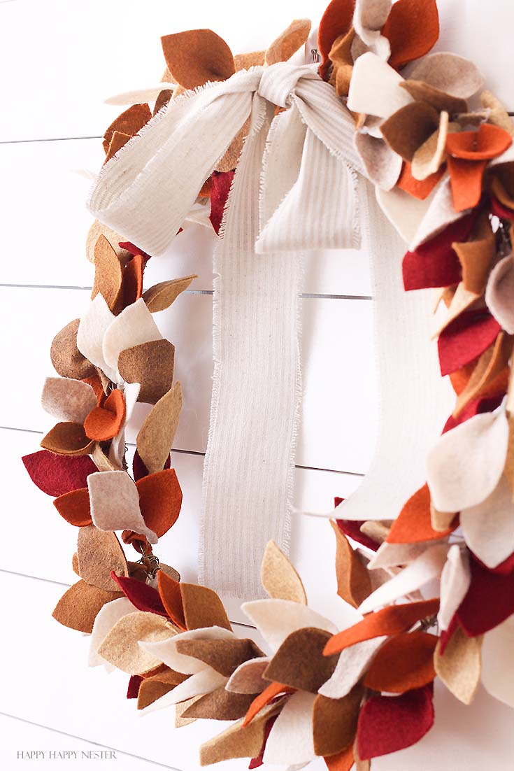 side shot of felted leaf wreath hanging on white wall