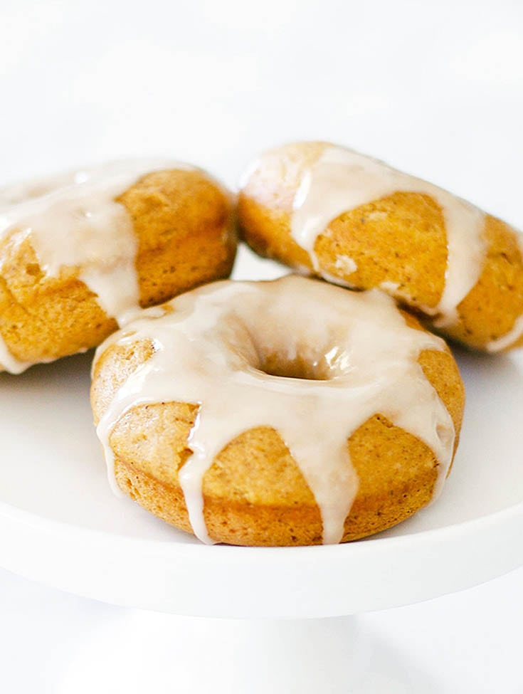 three pumpkin donuts with white icing on a white cake stand