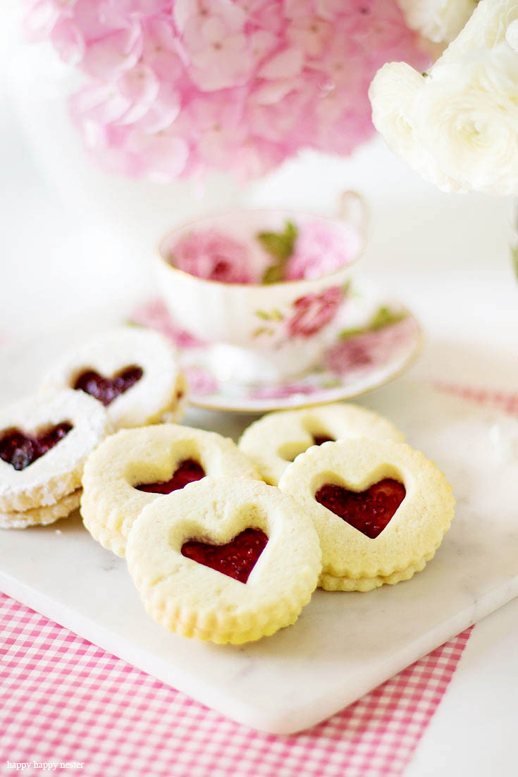 These delicious cookies are great year round. This Raspberry Filled Valentine's Heart Cookie Recipe is the perfect dessert for a dinner or a party. Give them away as a Valentine's Day gift for a friend. Sprinkle them with powdered sugar for an extra-amazing sugar cookie. Cookie | Baking | Valentine's Day Treats | Cookie Recipe | Raspberry Filled Cookies