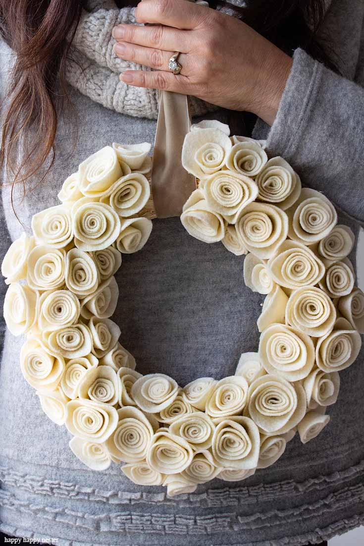 This Rosette Felt Wreath Tutorial makes a beautiful wreath. You'll find it easy to make. The neutral color will go with any decor, and it can be displayed all year long. So, make sure to create this felt flower wreath with these cute felt rosettes.