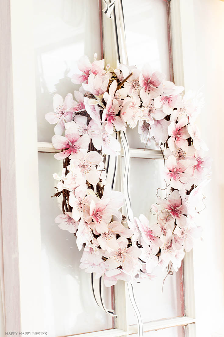 Paper flowers are perfect additions to a wreath. This easy How to Make a Paper Flower Wreath DIY is perfect for the spring. This wreath uses watercolor cherry blossoms that you cut out and glue to a grapevine wreath. It is a simple wreath that is beautiful and nice year round. The supplies include a wreath, paper, scissors, glue, and ribbon. #crafts #wreaths #spring