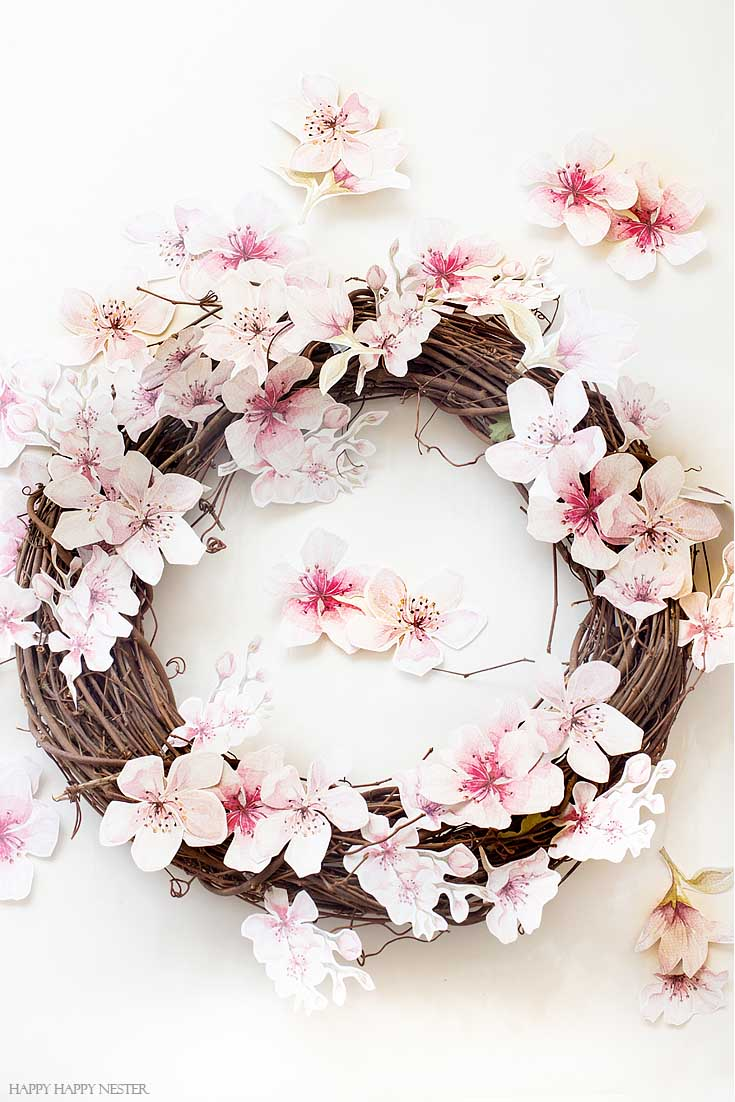 Make this easy and pretty wreath. This easy How to Make a Paper Flower Wreath DIY is perfect for the spring. This wreath uses watercolor cherry blossoms that you cut out and glue to a grapevine wreath. It is a simple wreath that is beautiful and nice year round. The supplies include a wreath, paper, scissors, glue, and ribbon. #crafts #wreaths #spring