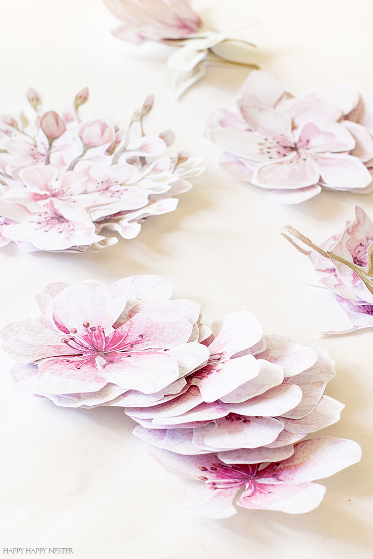 Get these free printable cherry blossom flowers for your wreath. This easy How to Make a Paper Flower Wreath DIY is perfect for the spring. This wreath uses watercolor cherry blossoms that you cut out and glue to a grapevine wreath. It is a simple wreath that is beautiful and nice year round. The supplies include a wreath, paper, scissors, glue, and ribbon. #crafts #wreaths #spring
