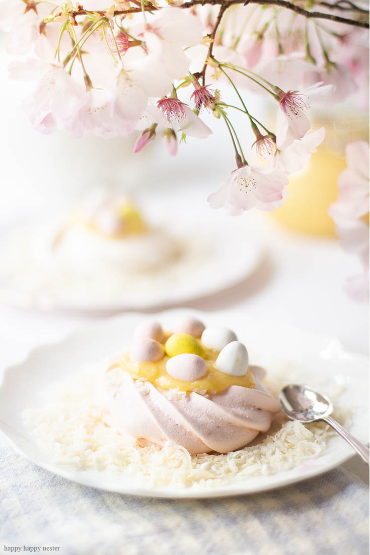 This Pavlova Recipe is so easy and the Mini Nests are so adorable. They are perfect for Easter, a spring dessert or year-round treat. Use different food colors to create cute fresh nests. Top the nests with lemon curd, whip cream, and Easter eggs. #baking #easter #desserts #easterdesserts #meringue #pavlova #lemoncurd
