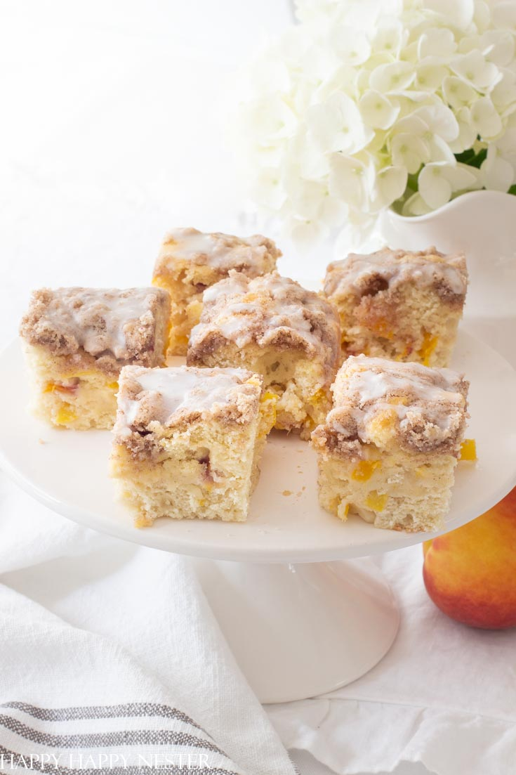 Here is the best ever peach buckle recipe and is the perfect summer dessert. This easy recipe is fresh and yummy with a cinnamon crumble and vanilla icing. Add a dollop of ice cream to accompany this summer cake. #recipes #peaches #freshfruitrecipes #desserts