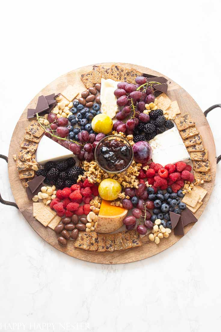 Need some Easy Appetizer Ideas for a Party, then you'll want to view this step by step tutorial. It shows how to build a fruit, cheese charcuterie board. This photo will be wooden round board with fruit, cheese and crackers. #appetizers #easyappetizers #charcuterieboard