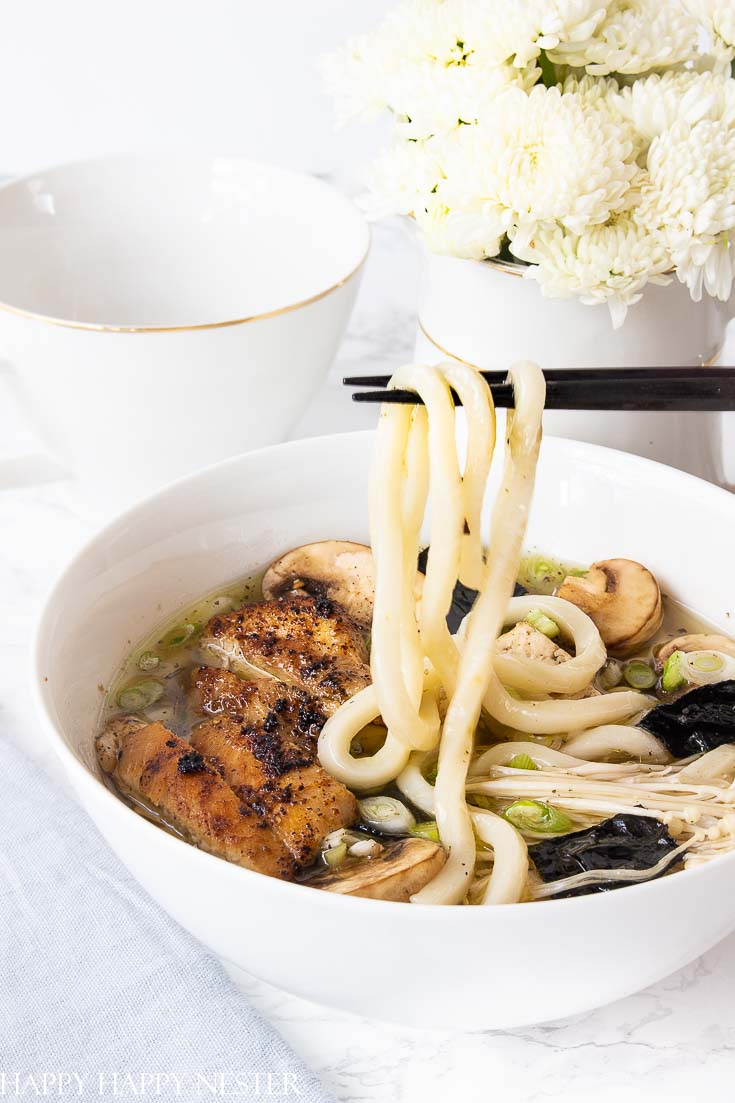 This Chicken Soup dish uses thick Japanese Udon Noodles that make this broth utter perfection. Find the tasty thick udon noodles at your Asian grocery store. Learn how to make this wonderful comfort food recipe. #chickennoodlesoup #soup #udon #japanesecuisine