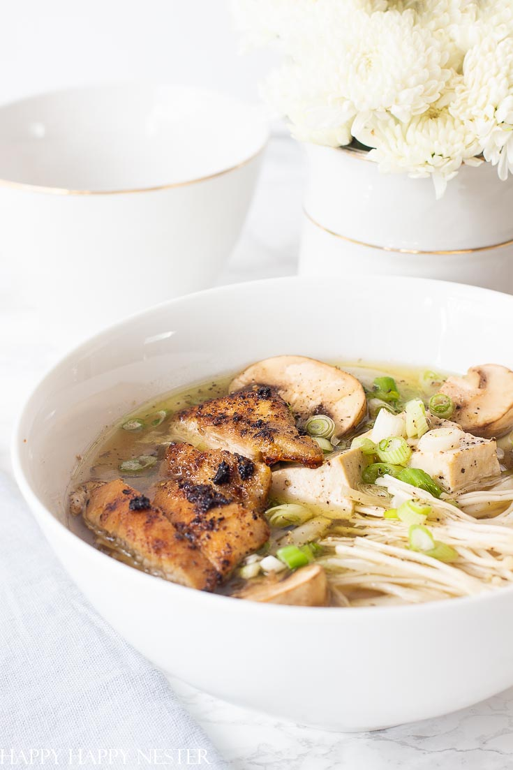 Homemade Chicken Noodles Soup in a big white bowl. This Homemade Chicken Noodle Soup goes beyond the traditional recipe. It uses the delicious Japanese Udon Noodles that make this broth utter perfection. Find the tasty thick udon noodles at your Asian grocery store. Learn how to make this wonderful comfort food recipe. #chickennoodlesoup #soup #udon #japanesecuisine