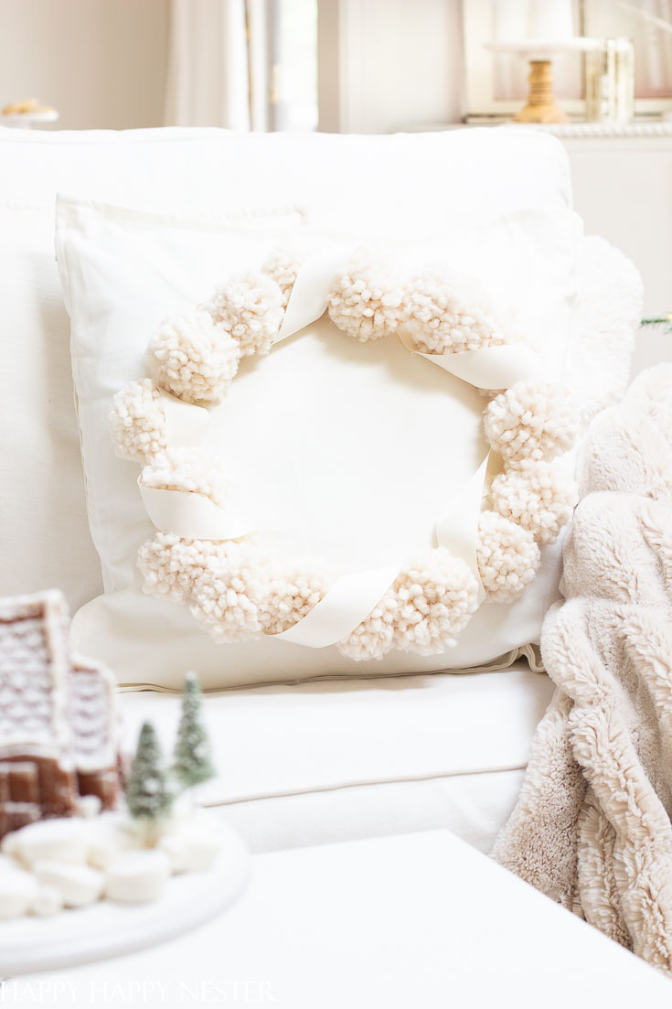 This adorable Christmas Pillow Craft Project is perfect for the holidays. It's an easy project to create and make it in your favorite holiday color. There are 13 pom pom projects in this blog post. #pompoms #crafts #holidaycrafts #pillowproject #pillows #christmas