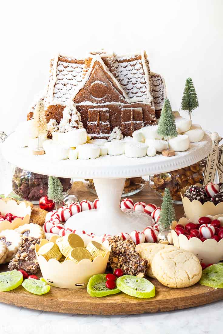Create this fun festive Christmas Dessert Charcuterie Board for the holidays. This board full of yummy treats includes my favorite cookies as well as a cute gingerbread cake as the centerpiece. #charcuterieboard #charcuterie #holidaydesserts #christmascookies