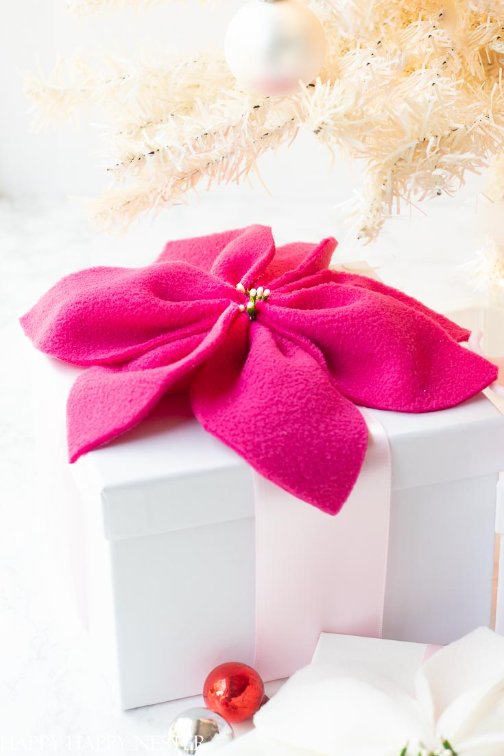 Create this adorable fleece poinsettia for the holidays! Make them in any color you like and place them on your Christmas gifts. #christmasprojects #easyflowers #crafts #flowers #poinsettia #paperflowers
