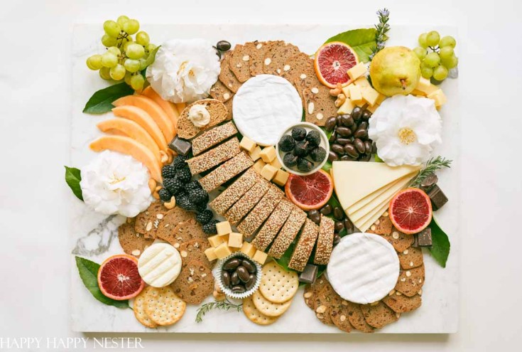 This impressive Charcuterie Board is elegantly styled with delicious cheeses, slices of bread, fruit, and rich chocolates. This epic appetizer will wow your family and friends. Learn how to create this amazing snack.