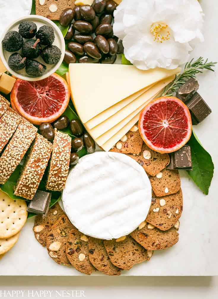 This impressive Charcuterie Board is elegantly styled with delicious cheeses, slices of bread, fruit, and chocolates. This epic appetizer will wow friends. Make this for any get together or meal. #charcuterieboard