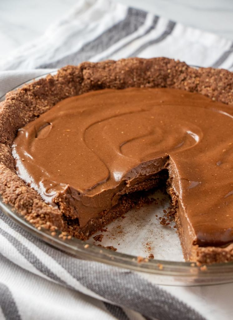 a whole vegan chocolate pie with a piece removed
