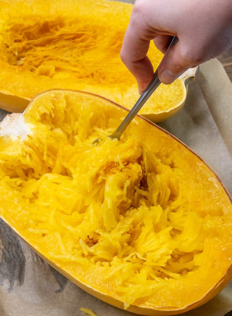 a fork scraping out the flesh of a cooked spaghetti squash