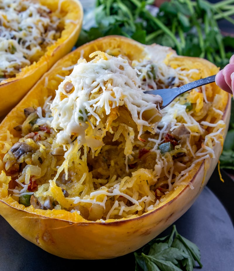 a cooked spaghetti squash with cheese and filling and a fork pulling out a bite