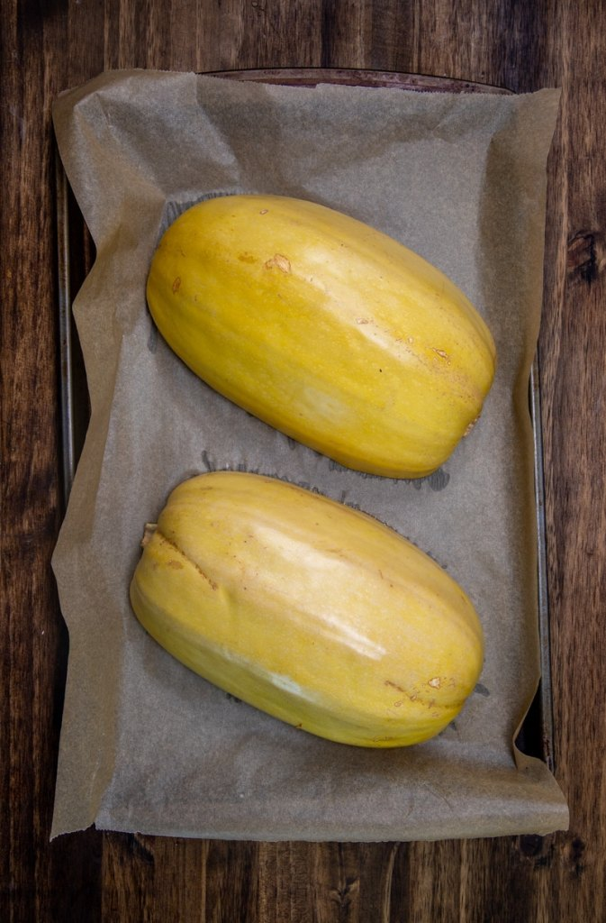 two spaghetti squash halves down on a parchment lined baking sheet