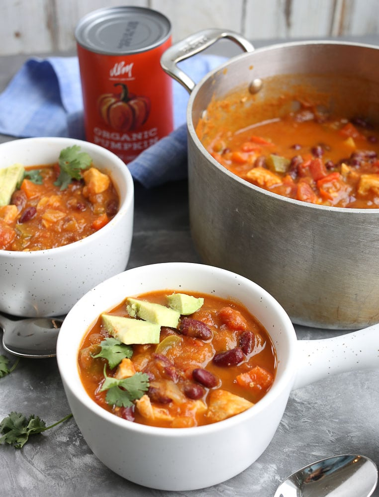 Chicken Pumpkin Chili recipe in a bowl with avocado and cilantro with the pot