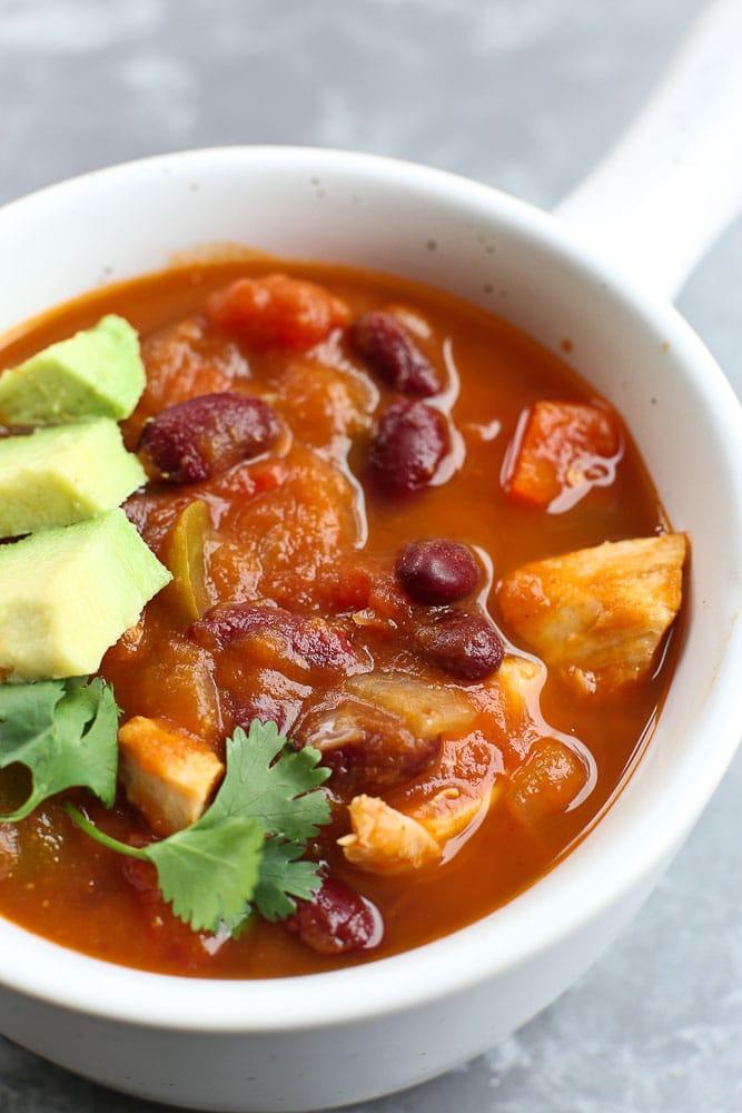 Pumpkin Chicken Chili recipe in a bowl with avocado and cilantro
