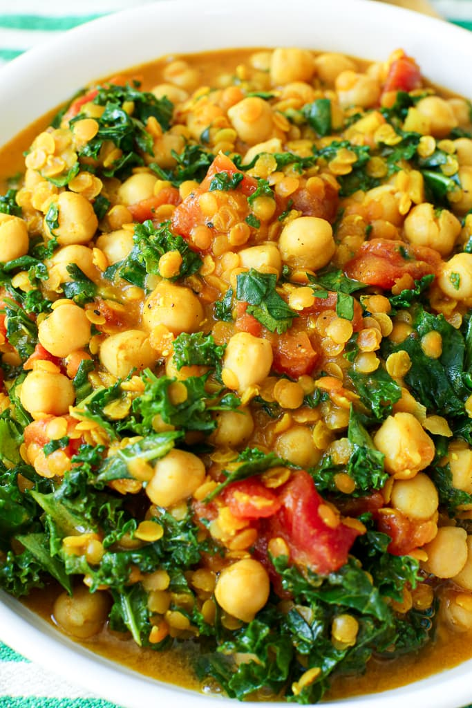 close up shot of chickpeas, kale, and lentils in a white bowl