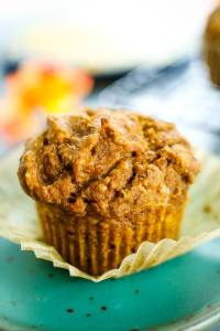 healthy pumpkin muffin on a green plate with a paper wrapper