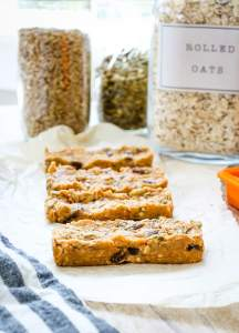 a line of 4 No Bake Granola Bars with oats and seed in the background