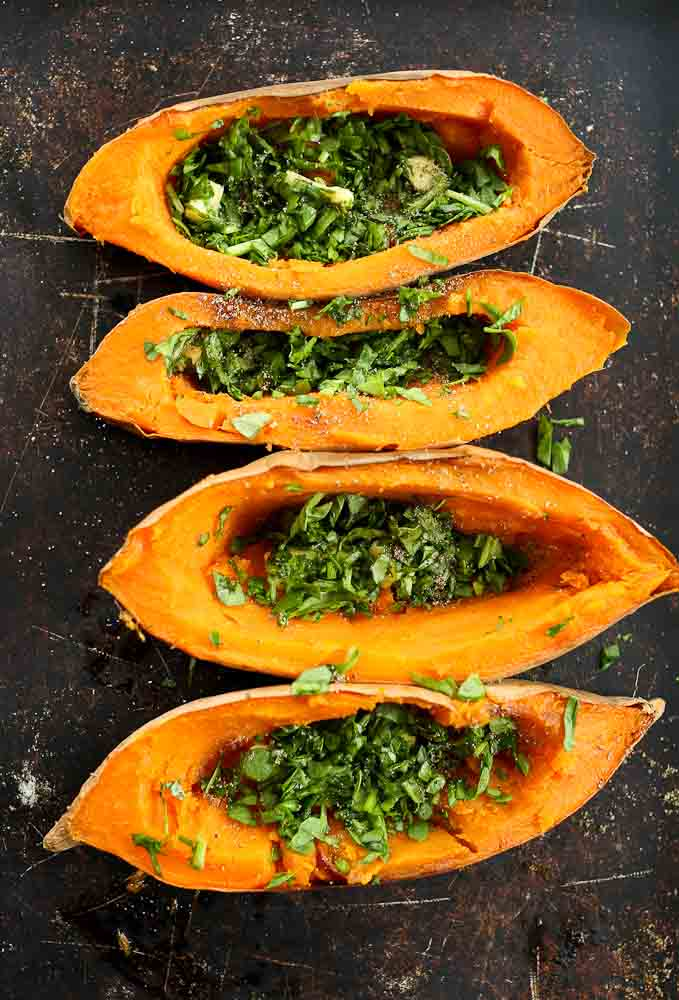 Step 2 of preparing Baked Eggs with Spinach in sweet potato boats--spinach and butter added