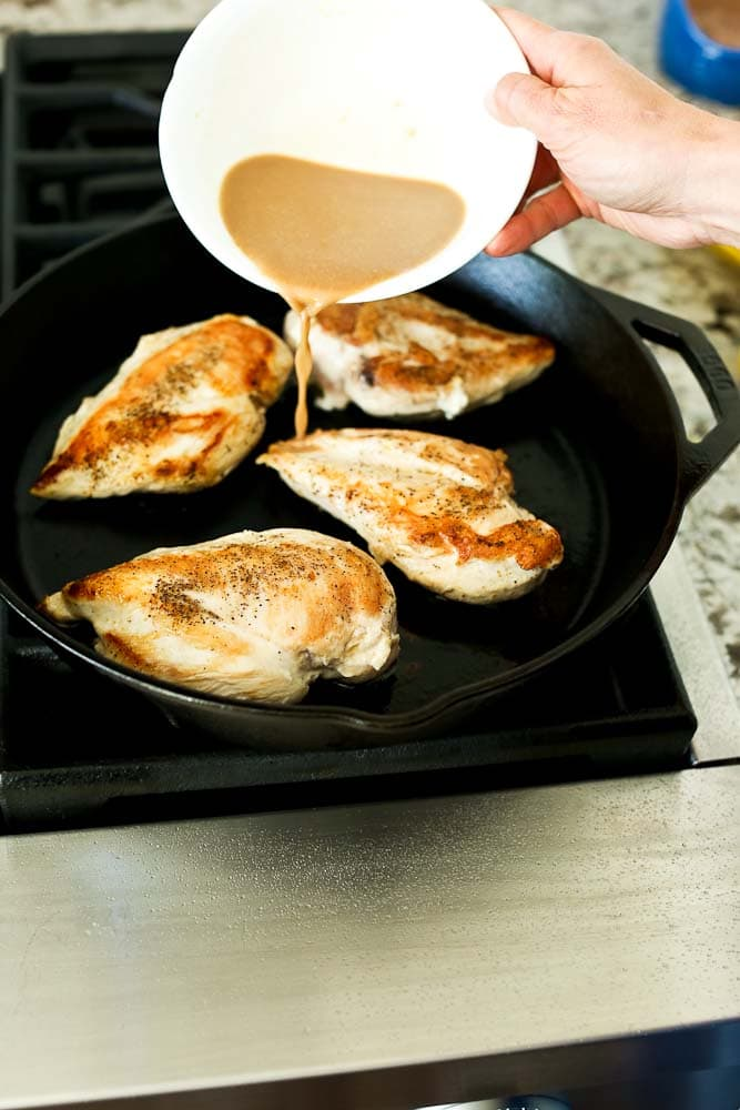 Adding liquid to the cast iron skillet with chicken breasts