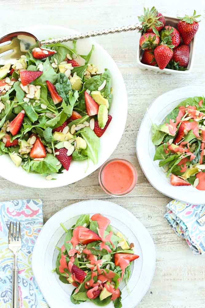 Strawberry Spinach Salad with Avocado and Strawberry Vinaigrette dressing set up on table
