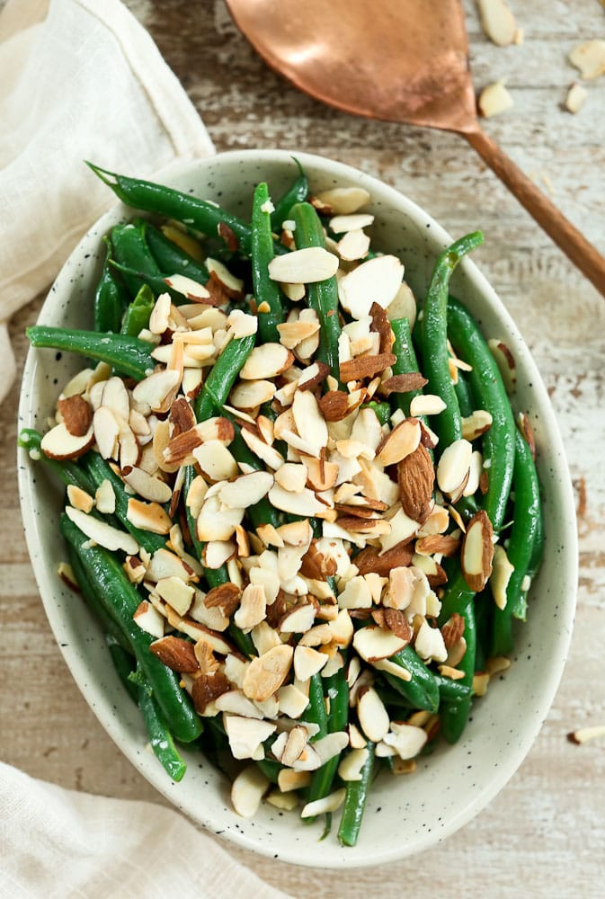 Garlic Butter Green Beans with Toasted Almonds recipe in a bowl with a copper serving spoon