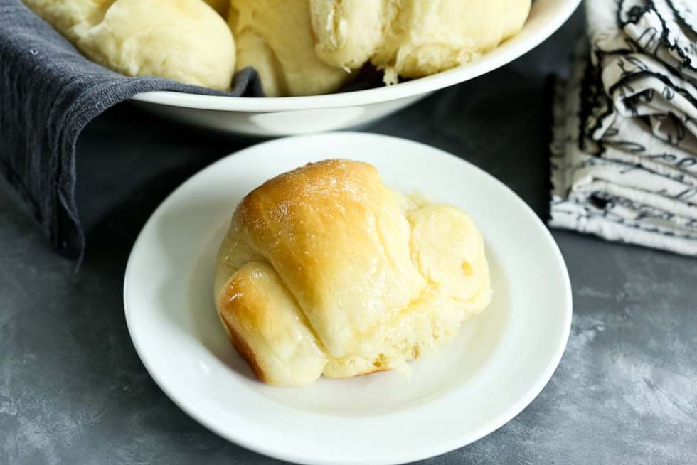 Perfect Bread Machine Dinner Rolls Recipe in a bowl with a gray napkin and on a plate