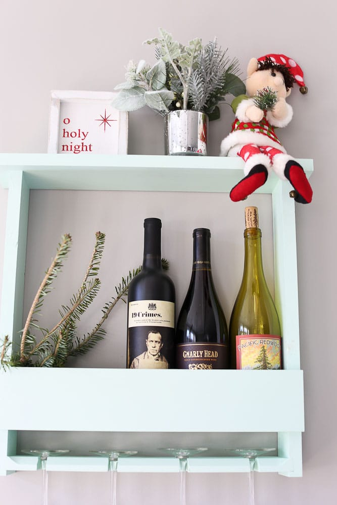 Dingle the original elf on the shelf--next to our wine bottles