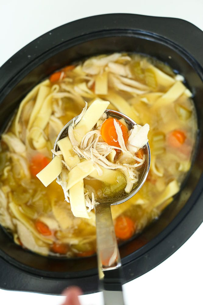how to make easy crockpot chicken noodle soup recipe ladle with chicken breast, noodles, and carrots coming out of pot