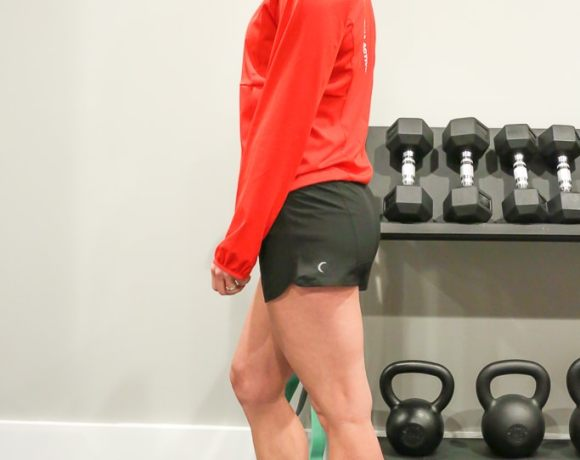Maryea Flaherty standing in front of a weight rack in a red jacket and black shorts, looking over her shoulder smiling