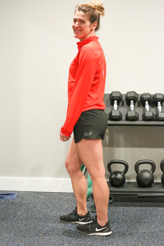Maryea Flaherty standing in front of a weight rack in a red jacket and black shorts, looking over her shoulder smiling and ready for her leg workout at home