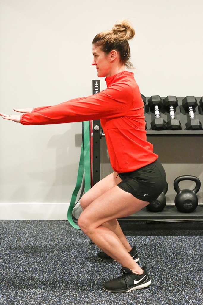 Maryea Flaherty in a red jacket and black shorts completing a squat exercise