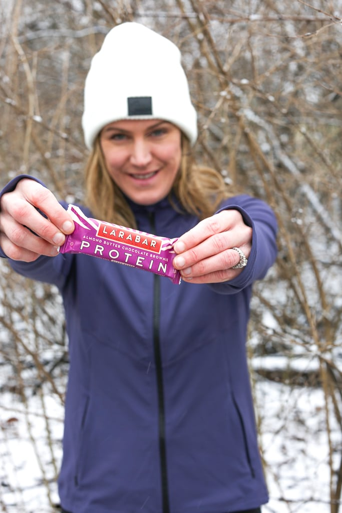 A woman in a purple jacket and white hat holding a Larabar in front of her snowy tree branches in the background