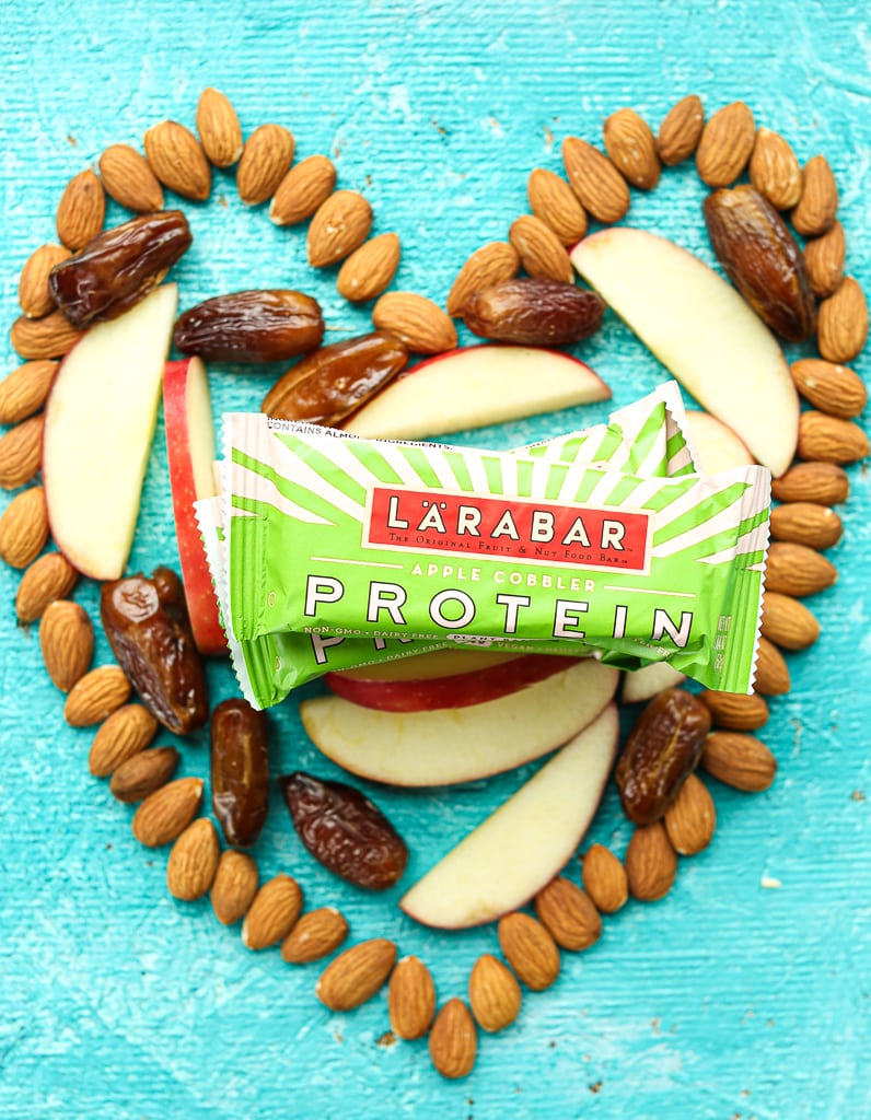 Almonds in the shape of a heart with dates, apples, and Larabar protein bars inside the heart